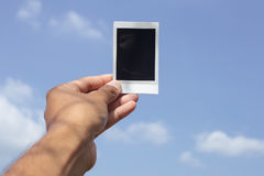 Polaroid in hand. With Blue sky background Royalty Free Stock Photos