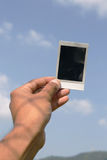 Polaroid in hand. With Blue sky background Royalty Free Stock Photo