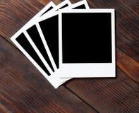 Polaroid instant photo frame. On old dark wood table Royalty Free Stock Photos