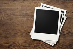 Polaroid phot frames on old wooden table Royalty Free Stock Photography
