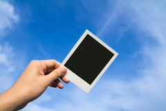 Polaroid photo frames. Hand holds a polaroid photo frame against blue sky Stock Images