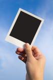 Polaroid photo frames. Hand holds a polaroid photo frame against blue sky Royalty Free Stock Images