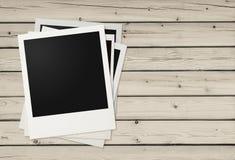 Polaroid photo frames on wooden background Stock Photos