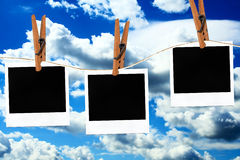 Polaroid photos. Hanging on a rope with clothespins against blue sky Stock Photos