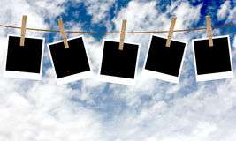 Polaroid photos hanging on a rope with clothespins Stock Image