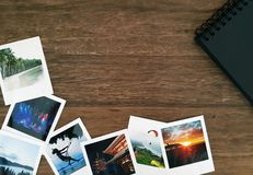 Polaroid pictures and a black spiral photo album on a wooden table with white space royalty free stock image