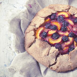 Polaroid of whole french galette with sliced apricots peaches and blueberries on tray rustic background Stock Images