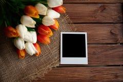 Polaroidbild mit schwarzem Raum und der Blumenstrauß von Tulpen auf dem braunen hölzernen Hintergrund lizenzfreies stockbild