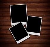 Polaroidfotos auf hölzerner Beschaffenheit. Lizenzfreie Stockfotos