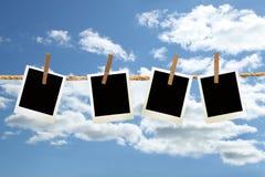 Polaroidfotos, die an einem Seil mit Clothespins hängen Lizenzfreie Stockfotografie