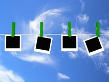 Polaroids hanging on line. Against blue sky Royalty Free Stock Image