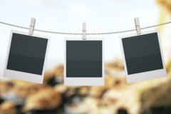 Polaroids on landscape. Three blank polaroids hanging on rope with clothespins on landscape background. Mock up, 3D Render Royalty Free Stock Photography