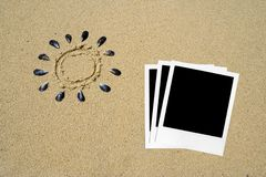 Polaroids photos in the sand. A group of polaroids photos and drawing of the sun in the sand made with shells royalty free stock image
