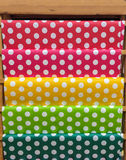 Polca roja, rosada, amarilla, verde y azul clásica colorida Dot Pattern Paper en el estante de madera para el trabajo de DIY Fotos de archivo libres de regalías