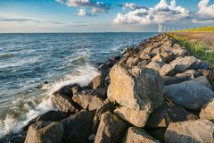 The polder dike with stone bollards along the Ijsselmeer at Flev. An inner lake in the Netherlands with waves striking on the stone dykes of the polder during Royalty Free Stock Images