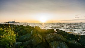 The polder dike with stone bollards along the Ijsselmeer at Flev. Sunset above a binary lake in the Netherlands with views over the water and the setting sun Stock Images