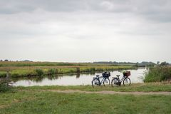 Dutch polder landscape with a stream and two bicycles. Polder landscape in the Dutch province of Noord-Brabant with a stream and two bicycles with baskets parked royalty free stock photography