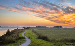 Polder landscape with winding cycling track. Dutch Polder landscape with winding cycling track along river under beautiful sunset Stock Photography
