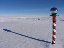 The Pole. The barber pole is located at the center of the Ceremonial South Pole. The flags of the original signatory nations to the Antarctic Treaty surround it royalty free stock images