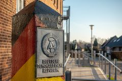 pole with the coat of arms of the GDR stands in a village stock photography