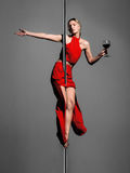Pole dance girl with wine. Pole dance girl in elegant red outfit holding a glass of wine Royalty Free Stock Photos