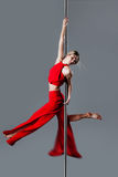 Pole dance girl. In elegant red outfit posing against gray background Royalty Free Stock Images