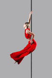 Pole dance girl. In elegant red outfit posing against gray background Stock Image