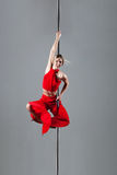 Pole dance girl. In elegant red outfit posing against gray background Royalty Free Stock Photo