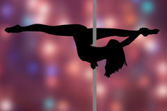 Pole dance. Girl with the pole. A girl is practicing pole dance with a pole. Position in the sagittal split inverted. Background with warm colors and bright Stock Image