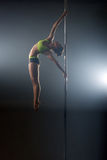 Pole dance. Graceful dancer performs acrobatic pas Stock Image