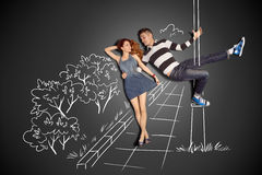 Pole dance. Happy valentines love story concept of a romantic couple against chalk drawings background. Male pole dancing on a lamppost while walking with Stock Photos