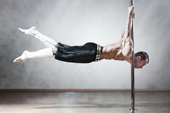 Pole dance man. Young strong pole dance man royalty free stock photo