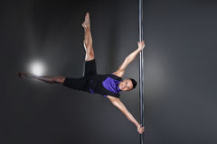 Pole dance man over black background with flashes Royalty Free Stock Images