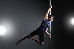 Pole dance man over black background with flashes Stock Images