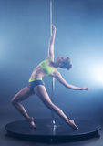Pole dance. Sexy girl froze in graceful pose Stock Images
