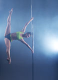 Pole dance. Strong girl froze in stretching pose Stock Photos