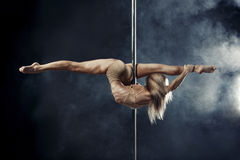 Pole dance. Young beautiful pole dance woman, sportive, flexible. Dark background Royalty Free Stock Images