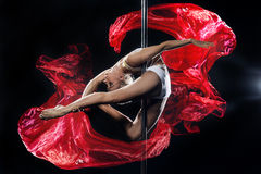 Pole dance. Young beautiful pole dance woman, sportive, flexible. Dark background and red silks Stock Photography