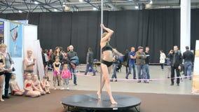 Pole dance, young teenager with acrobatic program on pylon,. KIEV - MAR 16: Young sportswoman show acrobatic program on pylon during Activesport exhibition ( stock video