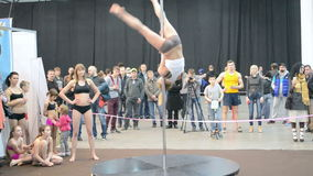 Pole dance, young teenager with acrobatic program on pylon,. KIEV - MAR 16: Young sportswoman show acrobatic program on pylon during Activesport exhibition (