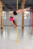 Pole dancer doing complicated figure Stock Image