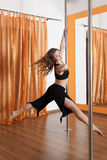Pole dancer in the flying in the air. Woman training pole dance in suspension walk pose Stock Photos