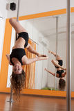 Pole dancer practicing. A female pole dancer athlete, in an upside down position Stock Images