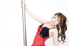 Pole dancer series. A pole dancer holding the pole with one hand Stock Image