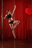 Pole dancer stands on pylon. Leap Stock Images