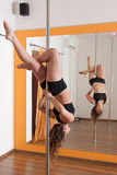 Pole dancer training. Woman training pole dance Stock Photos