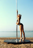Pole dancer woman against sea Stock Photography