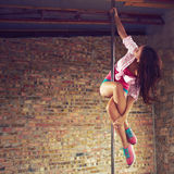 Pole dancer. Young pole dancer woman wearing colorful sports wear trains on grunge interior with brick walls, right side align, square composition Royalty Free Stock Photos