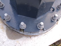Pole flange with heavy threaded galvanized studs and nuts on a concrete footing Royalty Free Stock Photo