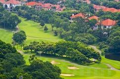Pole golfowe, z zielonymi drzewami i domami Fotografia Royalty Free